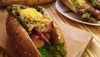 Хот-дог с беконом, листьями салата, сосиской, горчицей и сыром